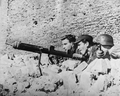 Powstańcy na stanowisku ogniowym, uzbrojeni w granatnik przeciwpancerny typu PIAT, 1944 r. (fot. AIPN)